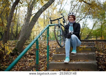 Photo of brunette sitting on stairs next to bicycle