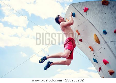 Photo of sportive man balancing on wall for climbing against cloudy sky