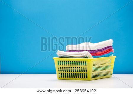Photo of stack of multi-colored towels in yellow basket on empty blue background.