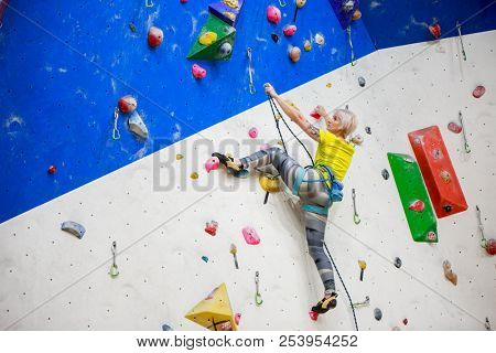Photo from back of young ahtlete woman in yellow T-shirt scrambles on wall for climbing at workout