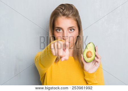 Beautiful young woman over grunge grey wall eating avocado pointing with finger to the camera and to you, hand sign, positive and confident gesture from the front