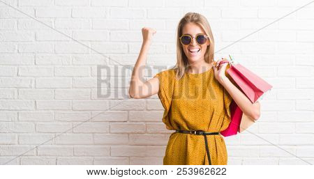 Beautiful young woman over white brick wall holding shopping bags on sales screaming proud and celebrating victory and success very excited, cheering emotion