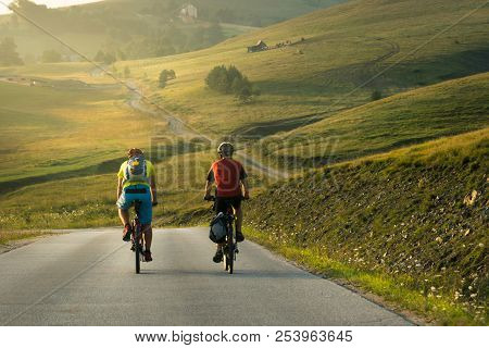 Cycling in countryside in summer. Lifestyle concept. Two man cycling in sunset in countryside. Lifestyle. Travel cycling in sunset in countryside hills. Cyclists travelers on the road in sunset. Lifestyles. Cycling. Bicycle. Sunset. Travel