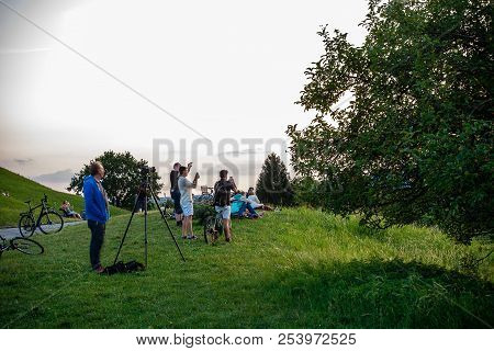Munich,germany-august 15,2018:people Appear Blurred While Taking Pictures Of The Setting Sun From A