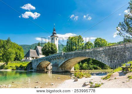 Bohinj Bridge And Church, Slovenia. Look To Old Historic Ancient Bridge And The Church Near The Bohi