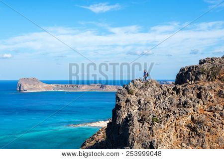 Traveler With A Backpack Stands On A Rock And Looks At The Panorama Of Crete Island, Greece