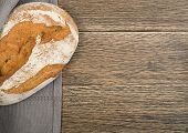 Homemade Freshly Baked Traditional Bread on Dark Wooden Table Top View with Copyspace. Whole Loaf of Rustic Italian Cereal Bread Made of Sourdough Dough with Space for Text poster
