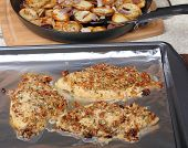 Catfish with cashew topping on a baking sheet with potatoes in background poster