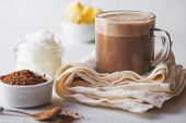 BULLETPROOF CACAO. Ketogenic keto diet hot drink. Cacao blended with coconut oil and butter. Cup of bulletproof cacao and ingredients on white background poster