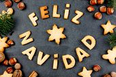 FELIZ NAVIDAD COOKIES. Words Merry Christmas en Spanish with baked cookies, Christmas decoration and nuts on black slate background. Christmas card for hispanic countries top view poster