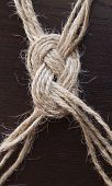 Knot from the jute twine on  wooden  background poster