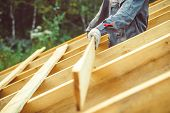worker roofer builder working on roof structure on construction site poster