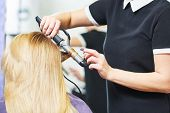 hairdo in beauty salon. hairdresser making coiffure with curl to wonam poster