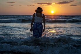 The Silhouette Of A Beautiful Young Woman In A Long Light Dress Entering The Sea During The Tide At