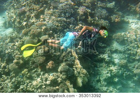 Scuba Diver Swims On Vibrant Coral Reef In The Sea. Diver Is Swimming Along A Tropical Reef