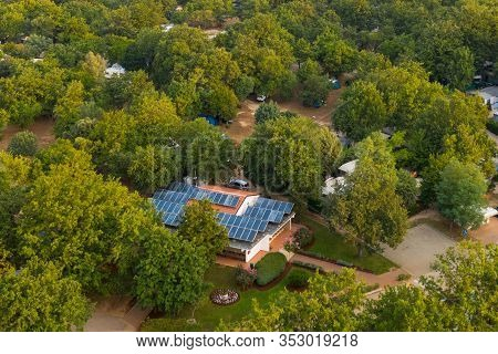 One-story Residential Building With Solar Panels On The Roof. The House Is Located In A Wooded Area.