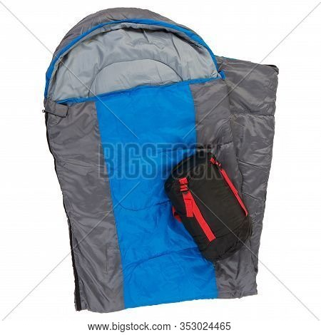 A Sleeping Bag With A Blue Stripe, Folded In Half, A Sleeping Bag In A Cover Lies On Top, On A White