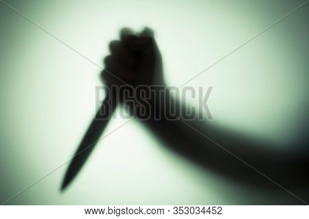 Silhouette of a man with a knife in his hand through frosted glass, killer or burglar