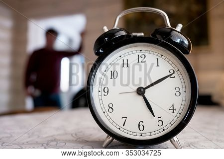Black alarm clock on the table and blurred male silhouette. Five o'clock time