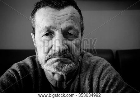 Elderly sad tired man close-up face, black and white photo