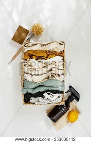 Reusable shopping bags and ingredients for eco home cleaning on white background.