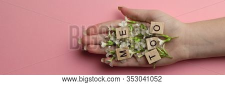 Phrase Me Too Made Of Wooden Letters In Hand Full Of Flowers On Pink Background, Top View. Stop Sexu