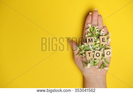 Phrase Me Too Made Of Wooden Letters In Hand Full Of Flowers On Yellow Background, Top View. Stop Se
