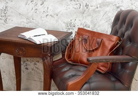 Leather Business Bag And Accessories In The Work Room With Gray Concrete Wall, Wood Table And Leathe