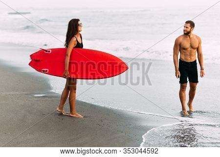 A Couple In Love On The Beach. Surfing In Bali Indonesia. Couple Of Surfers Walking On Coast In Indo