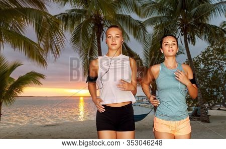 fitness, sport and healthy lifestyle concept - young women or female friends with earphones wearing armbands with smartphones and running over palm trees on tropical beach on background
