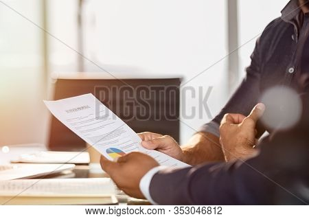 Businessman showing a document to his colleague. Businessman analyze graphs and charts with manager. Two businessmen reading business contract for merger and acquisition.