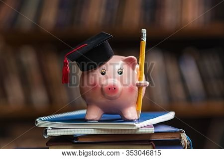 Pink piggy bank wearing graduation cap and holding pencil on pile of books in college library. Student loan and debt concept. Close up of piggybank with black graduate hat.