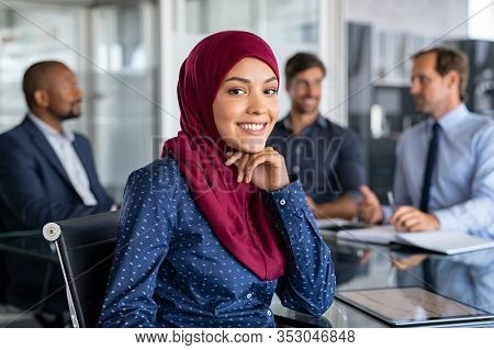 Beautiful arab businesswoman in hijab looking at camera and smiling while working in office. Portrait of muslim business woman working and at conference with multiethnic colleagues in background.