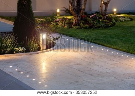 Marble Tile Playground In The Night Backyard Of Mansion With Flowerbeds And Lawn With Ground Lamp An