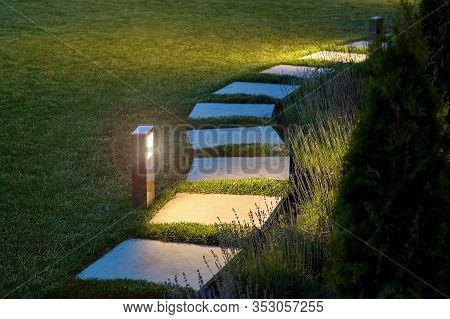 Marble Path Of Square Tiles Illuminated By A Lamp Glowing With A Warm Light In A Night Garden With A