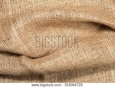 Crumpled Burlap Textile, Close Up View. Brown Burlap Fabric, Abstract Background. Texture Of Hopsack