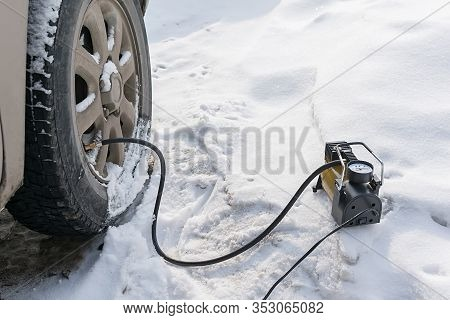 Pump, Automobile Compressor For Inflating Tires With Air Stands In The Winter On The Snow And Pumps