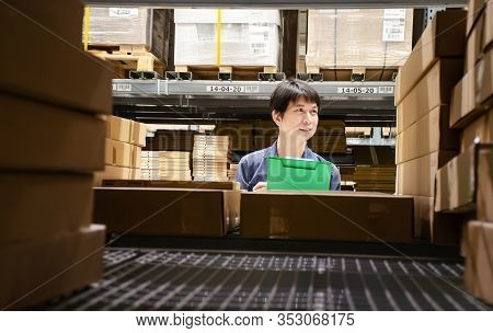 Asian Manager Man Doing Stocktaking Of Products Management In Cardboard Box On Shelves In Warehouse