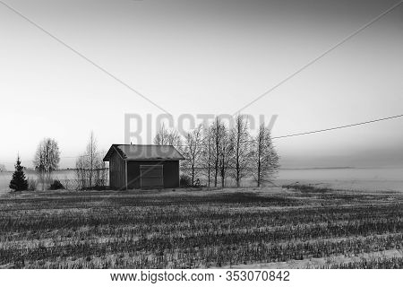 A Small Hut Stands On The Snowy Fields Of The Rural Finland. The Sun Sets And The Air Is Getting Col