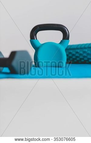 Home Gym Concept, Blue Yoga Mat With Kettlebell Foam Roller And Dumbbell Shot At Shallow Depth Of Fi