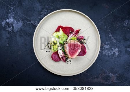 Japanese gourmet fried tuna fish steak tataki with pak choi, witloof and red beet offered as top view on a modern design plate with copy space
