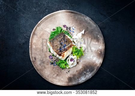 Gourmet fried European skrei cod fish filet with rapini broccoli rabe and noodles as top view on a modern design plate with copy space