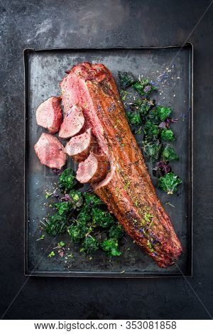 Barbecue dry aged venison tenderloin fillet steak and saddle natural with kalette offered as top view on a rustic board with copy space