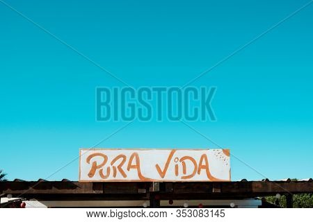 closeup of a sign with the text pura vida, pure life in spanish, handwritten in it, against the blue sky with a large blank space on top