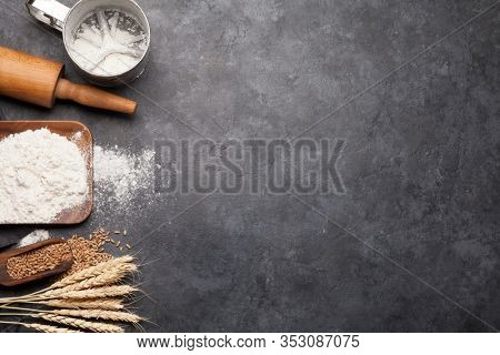 Bread ingredients. Wheat, flour and kitchen utensils on stone table. Homemade cooking concept. Top view flat lay with copy space