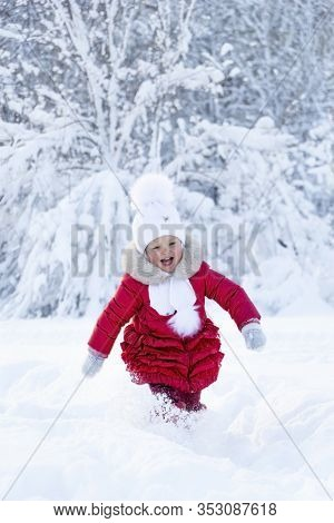 A Beautiful Little Girl In A Red Coat And White Hat With A Scarf Runs Along A Snowy Path In A Winter