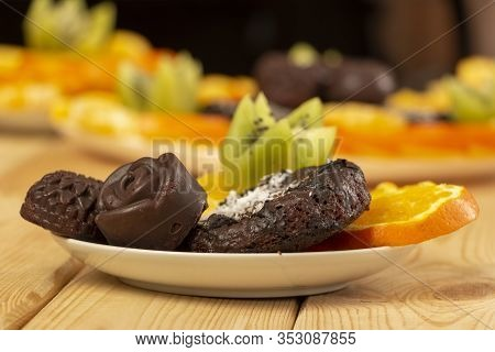 Chocolate Candies And Cookies Sprinkled With Coconut Flakes Lie With Chopped Fruits On A White Sauce