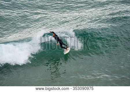 Sarges, Portugal - January 22, 2020: Surfers Catch Large Waves At The Beach At Praia Do Beliche In T