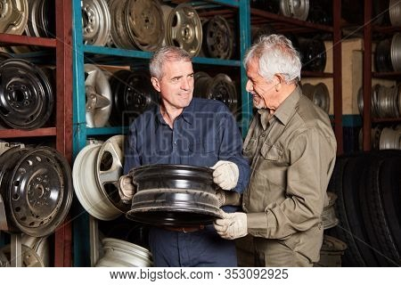 Two mechanics with car rims for wheel changes in spare parts stock of a car repair shop