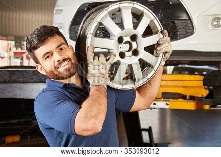 Young man as mechanic apprentice with car rim while changing wheels in the car workshop
